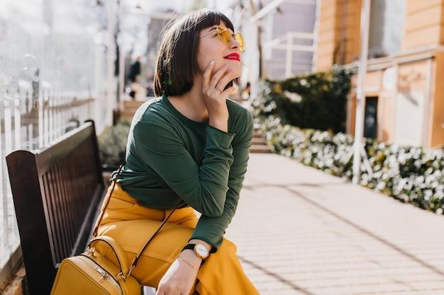 녹색 스웨터 벤치에 놀 아 요에 매력적인 금발 소녀. 거리에서 꿈꾸는 포즈 선글라스에 화려한 아가씨의 야외 초상화.