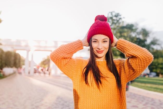 Attraente donna dai capelli castani in maglione arancione alla moda sorridente sulla città