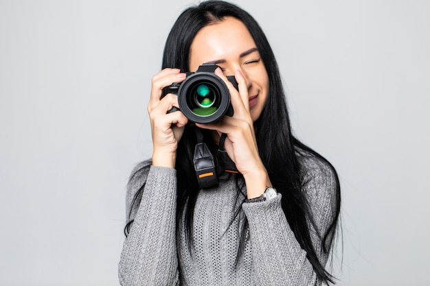 Attractive brunette aims her camera. composing a photograph in studio, isolated on gray wall
