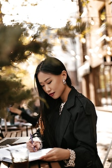 Attractive brunette asian woman in stylish black trench coat sits outside, makes notes in her notebook