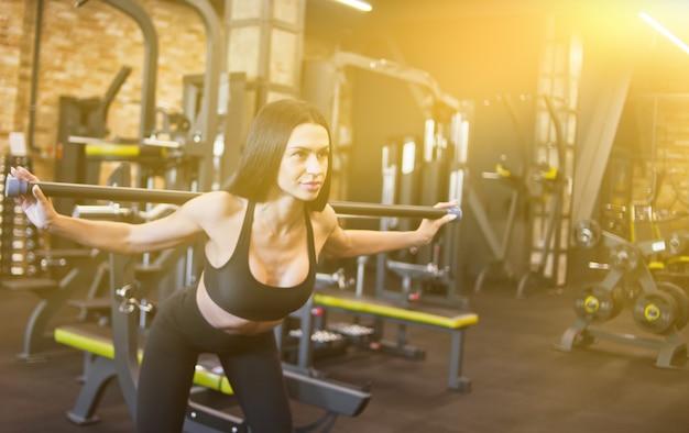 체육관에서 그녀의 시체를 기울이기 그녀의 어깨에 바디 바 체조 운동을 하 고 매력적인 갈색 머리 선수