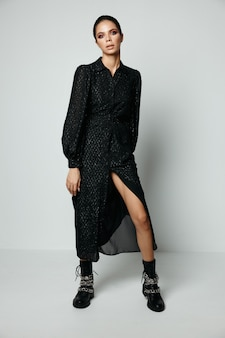 매력적인 갈색 머리 밝은 메이크업 패션 검은 드레스와 부츠.