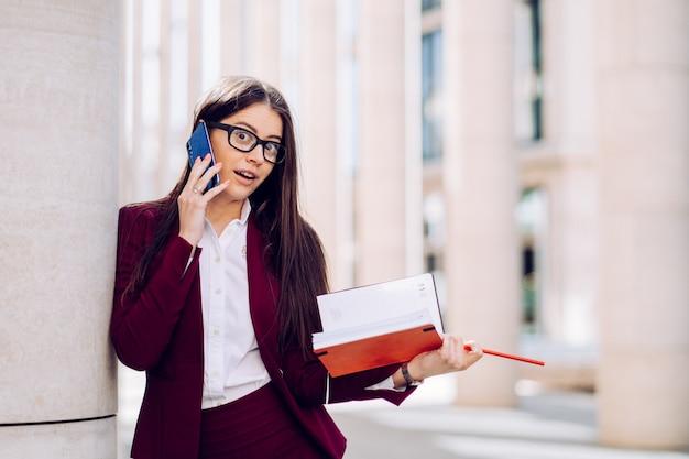魅力的なブルネットビジネスの女性は彼女のパートナーと話している間にニュースにショックを受けた、携帯電話と日記を屋外に保持
