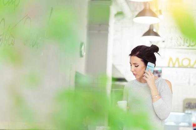 現代のカフェでクライアントと携帯電話で話している魅力的なブルネットの実業家