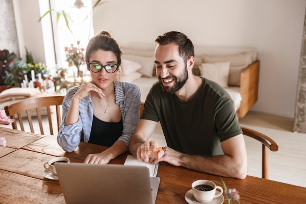 Attractive brunette couple man and woman drinking coffee and working on laptop together while sitting at table at home