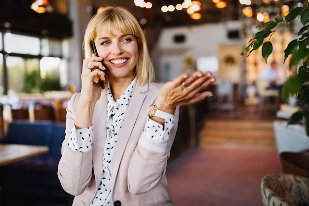 Attractive brunette coworker businesswoman talking on mobile phone with client