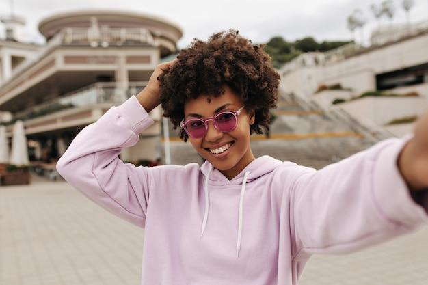 Attraente donna riccia bruna in felpa con cappuccio viola, occhiali da sole rosa sorride sinceramente, si rallegra e si fa selfie all'esterno