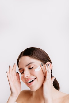 Attractive brunette enjoying spa procedure on isolated wall. smiling girl applies moisturizer.