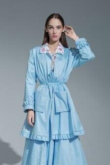 灰色のスタジオの背景に青いデザイナースーツでポーズをとって魅力的なブルネットファッションモデル