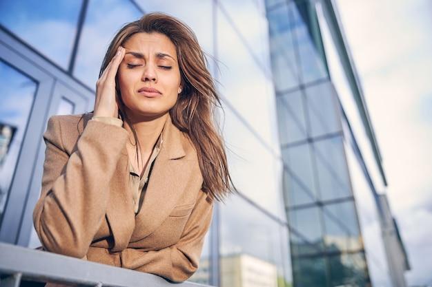 Привлекательная брюнетка женщина плохо себя чувствует на фоне небоскребов в деловом районе города