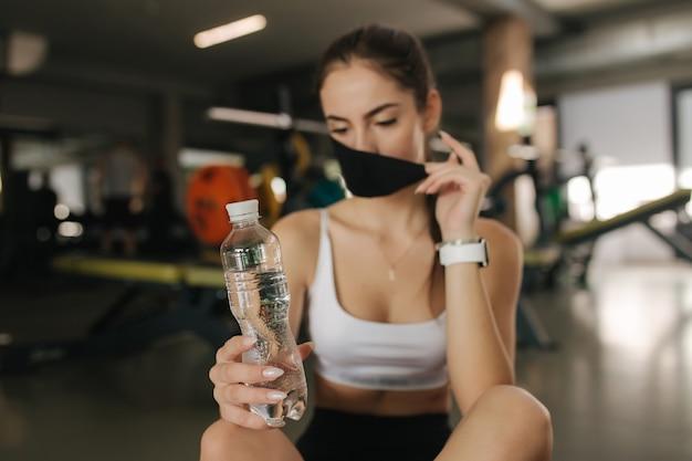 매력적인 갈색 머리 여성 체육관에서 휴식이 있습니다. 보호 마스크에 여자입니다. 여자는 바닥에 앉아있는 동안 물을 dring 마스크를 벗고