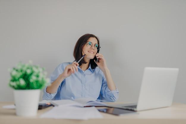 魅力的なブルネットの女性ジャーナリストは、携帯電話を介して会議を手配し、ラップトップコンピューターで新しい記事に取り組んでいます