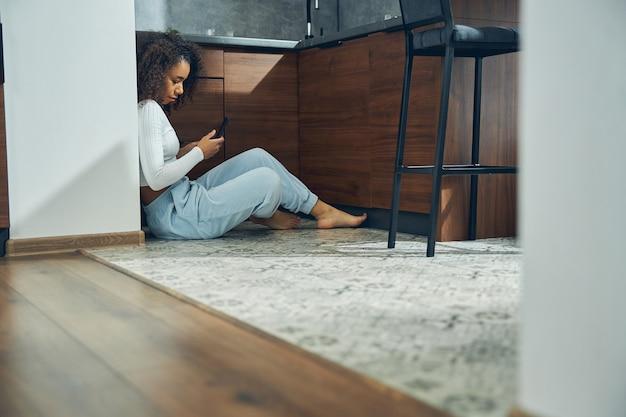 그녀의 모바일을 사용하는 동안 부엌에서 바닥에 혼자 앉아 매력적인 갈색 머리 여성