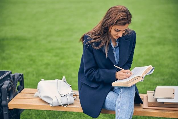 외부 벤치에서 공부하는 동안 좋은 날씨에 앉아 매력적인 갈색 머리 여자 학생