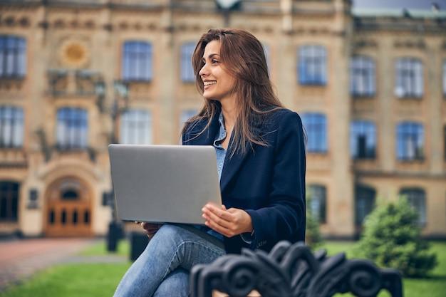 대학 외부에서 혼자 작업하는 동안 웃 고 그녀의 무릎에 노트북과 매력적인 갈색 머리 여자 학생