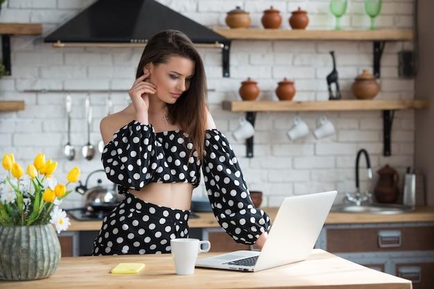 Привлекательная брюнетка девушка-блоггер в платье в горошек сидит на уютной кухне и читает новости на ноутбуке за деревянным столом.