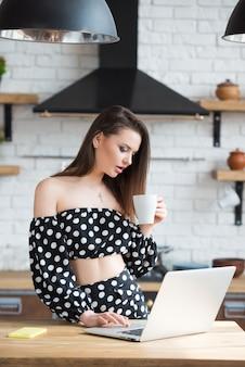 Привлекательная брюнетка девушка-блоггер в платье в горошек сидит на уютной кухне, пьет чай с кофе и читает новости на ноутбуке за деревянным столом.