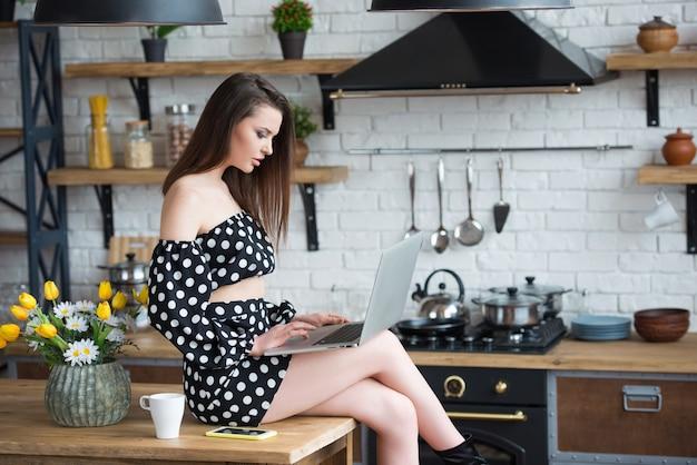 Привлекательная брюнетка девушка-блоггер в платье в горошек сидит на уютной кухне с ноутбуком за деревянным столом.