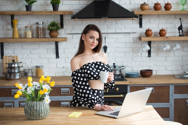 Attractive brunette girl blogger in a polka dot dress sitting in the cozy kitchen, drinking coffee tea and reading news on laptop at the wooden table.