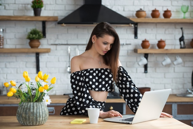 Attractive brunette girl blogger in a polka dot dress sitting in the cozy kitchen with laptop at the wooden table.