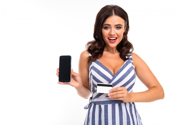 白い壁に彼女の手で電話とクレジットカードでネックラインと縞模様のドレスの魅力的なブルネットの少女