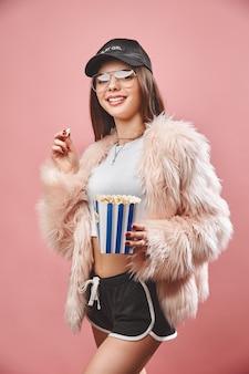 Привлекательная брюнетка в искусственно-розовом меху с попкорном в руке в черных шортах и белом топе ...