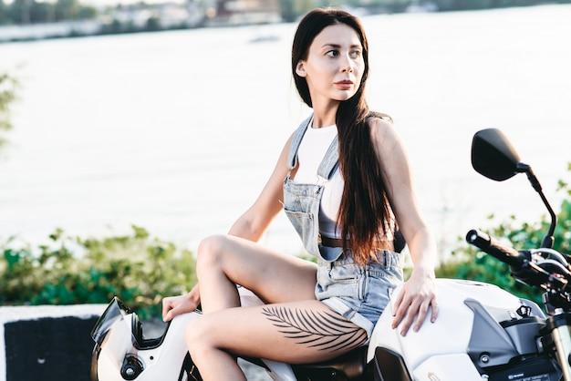 魅力的なブルネットの女の子が白いスズキgsrのオートバイに座っている