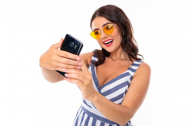 Attractive brunette girl in a striped dress and glasses makes selfie on the phone on a white wall