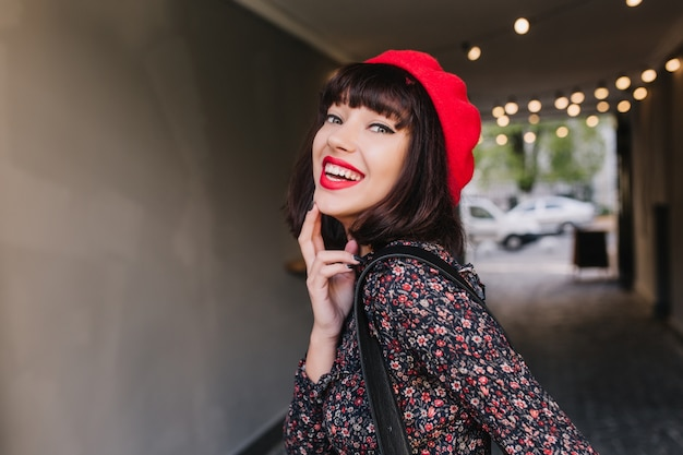 Attractive brunette girl in stylish vintage outfit coquettishly poses with sincere smile touching her chin. close-up portrait of elegant young woman in trendy french clothes laughing and having fun