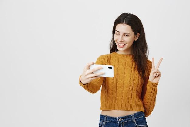 스마트 폰에 selfie를 복용하는 매력적인 갈색 머리 여자