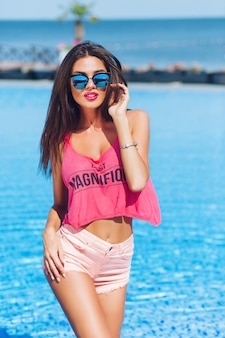 Attraente ragazza bruna con i capelli lunghi è in posa per la fotocamera vicino alla piscina. sta guardando alla telecamera.
