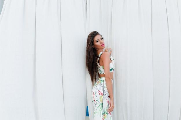 長い髪を持つ魅力的なブルネットの少女は、屋外の長い白いカーテンに近いポーズをとっています。彼女はカメラを見ています。