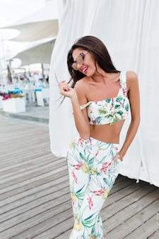 長い髪を持つ魅力的なブルネットの少女は、白いカーテンの近くの海辺でポーズします。彼女は髪に触れて、脇に寄り添っています。