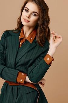 Привлекательная брюнетка гламур макияж пиджак мода бежевый фон