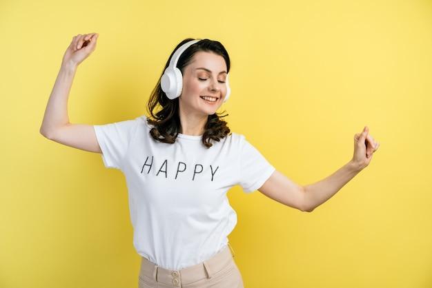 楽しんでいる魅力的なブルネット。彼女はヘッドフォンで音楽を聴き、踊ります。