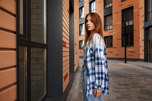 茶色の建物の都会的なスタイルの近くの格子縞のシャツの魅力的なブルネット