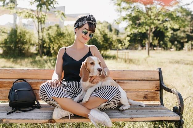 足を組んでビーグル犬をなでて座っている縞模様のズボンの魅力的なブルネットの女性。晴れた日に革のバッグの近くに子犬と一緒にベンチで休んでいるスタイリッシュな笑顔の女の子