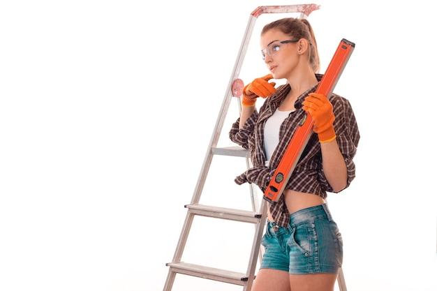 魅力的なブルネットの女性は、スタジオで白い背景に分離されたはしごでアパートを改装します