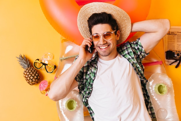 Attractive brunette man in plaid shirt and white t-shirt with smile talking on phone. guy in hat and sunglasses lying on inflatable mattress.