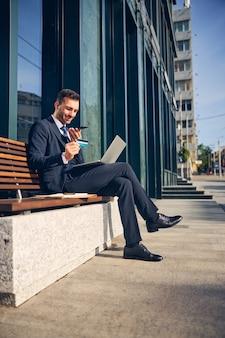가제트와 함께 벤치에 앉아 신용 카드를 들고 스마트 폰에 말하는 매력적인 갈색 머리 남자