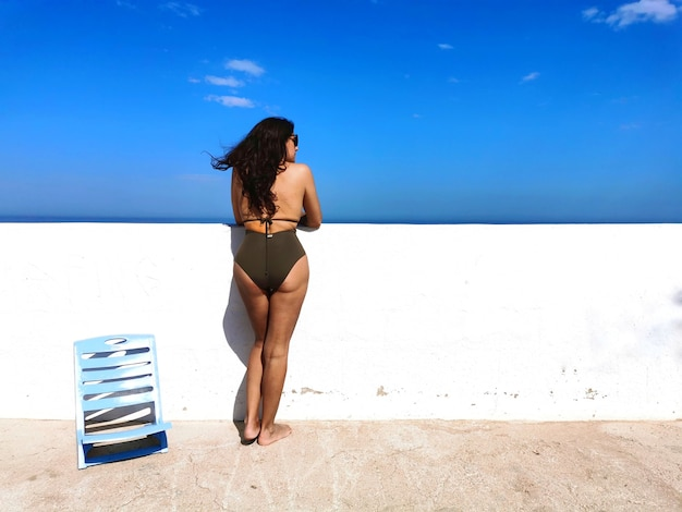 日光浴と青い空とビーチの日を楽しんでいる魅力的なブルネットの中年スペイン人女性