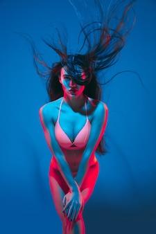 ネオンの光の青い壁に魅力的なブルネットのモデル。飛んでいる髪と暗いメイクでポーズをとっている下着の美しい女性。官能性、スタイル、ファッション業界、キャラクターの概念。