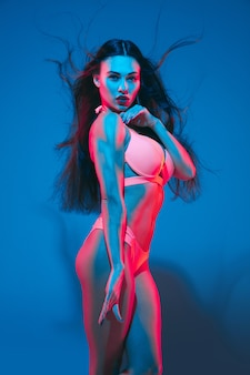 네온 불빛에 파란색 벽에 매력적인 갈색 머리 모델. 비행 머리카락과 어두운 메이크업으로 포즈를 취하는 속옷에 아름다운 여성. 관능, 스타일, 패션 산업, 캐릭터의 개념.