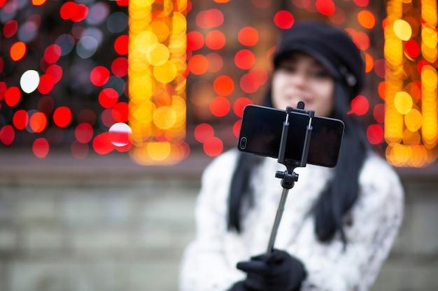 キャップを身に着けている魅力的なブルネットのモデル、ぼやけた光で通りで自画像を撮ります。テキスト用のスペース