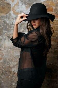 グランジの壁の近くでポーズをとる帽子と黒のブラウスを身に着けている魅力的なブルネットモデル