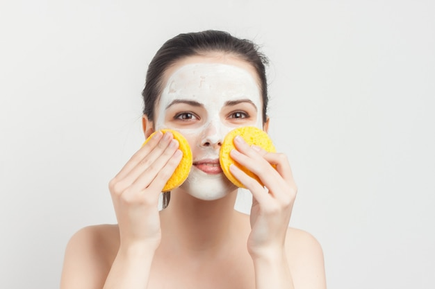 Attractive brunette naked shoulders face mask hand sponge skin care