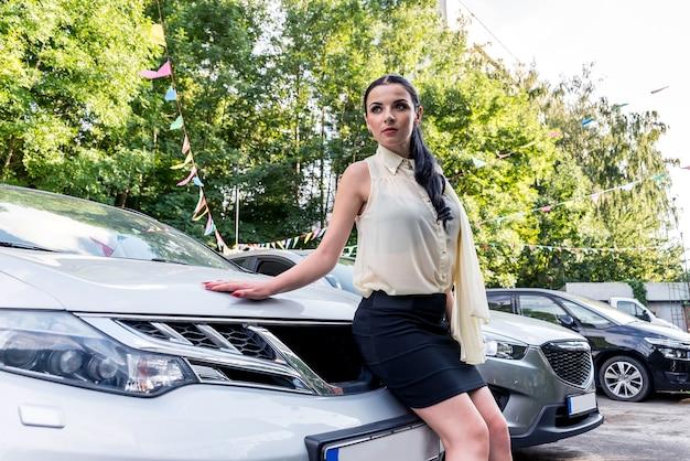 Привлекательная брюнетка позирует на капоте новой машины