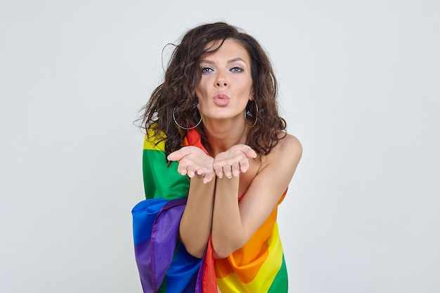 Attractive brunette posing with the flag of the lgbt