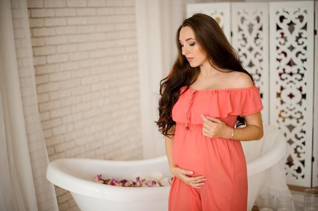 Привлекательная брюнетка беременная женщина одета в платье на фоне ванны с лепестками роз