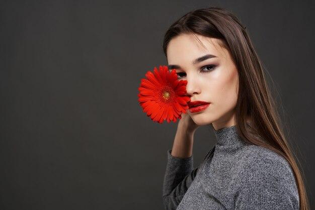 魅力的なブルネットの赤い花の魅力の化粧品のクローズアップ
